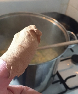 Bandaged thumb in front of a saucepan on the stove